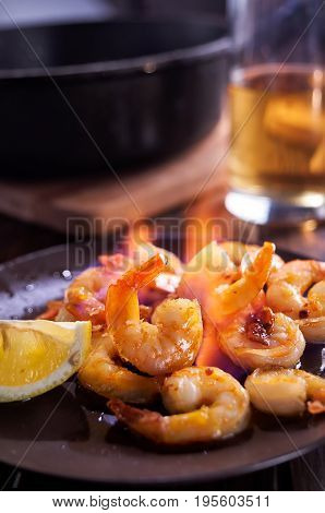 Schrimps flambe on plate with glass of beer on background. Vertical shot.