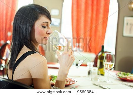 Woman tasting a glass of white wine in a restaurant