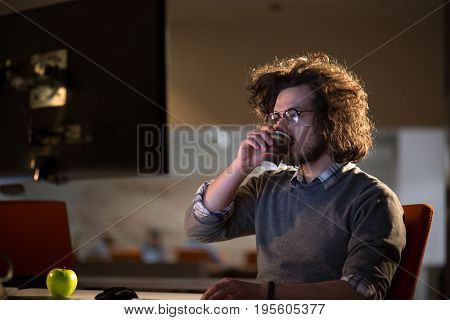 Tired businessman working late doing overtime in office at night drinking coffee to go on.