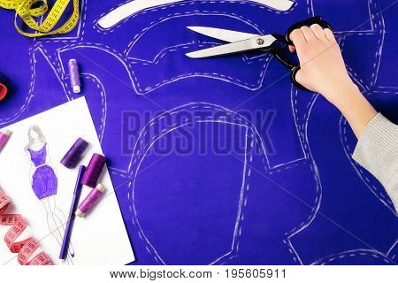 Workplace of a dressmaker: scissors pattern needles textile sketch sewing spools and measure tape. Girl holding scissors
