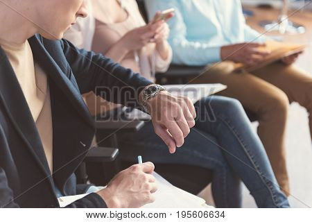 Close up of hands of serious man sitting on chair and looking at his handwatch. He is checking time while making some notes by pen on paper. Woman and man in queue next to him on background
