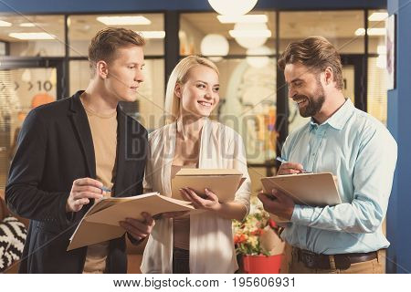 Two happy men and woman standing in office room and communicating with each other. Everybody is holding papers and pens. Bearded guy with clip board is laughing cheerfully while their conversation
