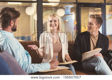 Portrait of jolly young woman sitting on office sofa with two men and talking about something funny. Everybody is holding paper files with documents. Bearded guy is writing by pen and using clipboard