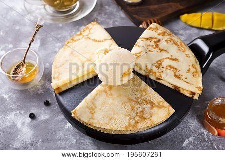 Dessert - Pancakes with mango Ice Cream and honey on stone background, flat lay