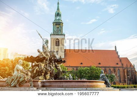 Morning view on Neptune fountain with saint Mary church in Berlin city