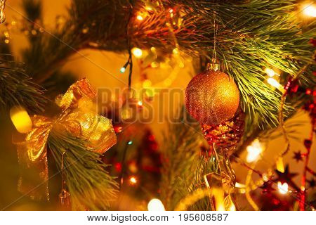 Golden bow  and ball on a background of green Christmas tree branches