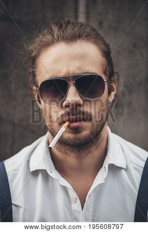 Close-up Portrait Of Handsome Bearded Young Man In Sunglasses Smoking Cigarette And Looking At Camer