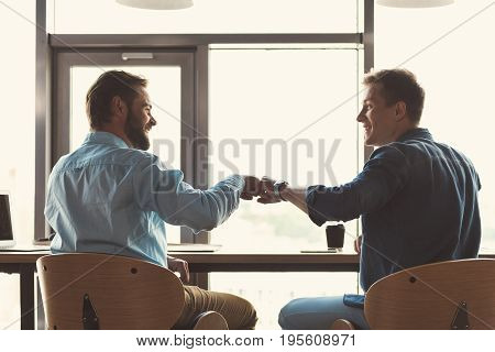 Two jolly young man are sitting at desk facing huge office window. They are turning to each other on chairs with toothy smiles and giving friendly hi by fists. Dark shadow and focus on their back