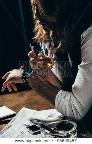 Young Long Haired Man Holding Glass Of Alcohol Beverage And Smoking Cigar