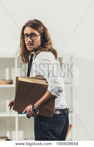 Stressed Young Businessman In Eyeglasses Holding Folders While Standing And Working In Office