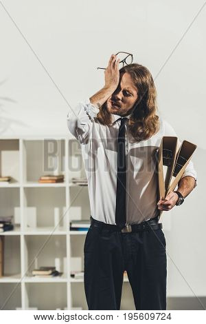 Tired Young Businessman Holding Eyeglasses And Folders While Standing In Office