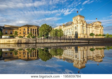 Morning cityscape view on the famous Reichstag building with beautiful reflection in the water in Berlin city