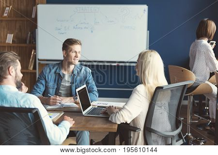 Happy young men and woman are sitting at square desk in open space room and discussing some job issues with joy. One guy is writing down information in his notepad and blonde girl is using laptop