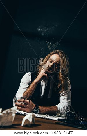Handsome Stylish Young Man Drinking Alcohol And Smoking Cigar While Sitting At Table