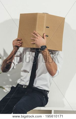 Stylish Young Businessman In Formal Wear Hiding Face With Folder In Office