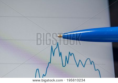 blue pen showing graph point on the screen