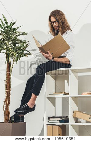 Stylish Young Long Haired Businessman In Eyeglasses Holding Folder While Sitting On Bookshelf In Off