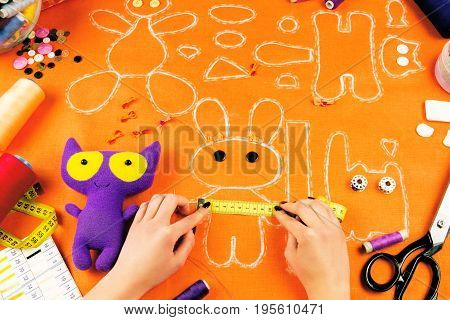 Workplace of a tailor: fabric spools measuring tape buttons needles bows toys and drawings. Girl measuring drawn rabbit with the measuring tape