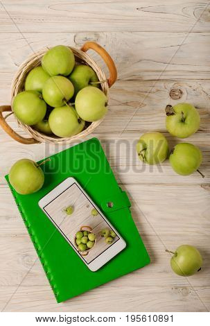 Green apples in a basket green notebook and white phone on a light wooden background. Selective focus.