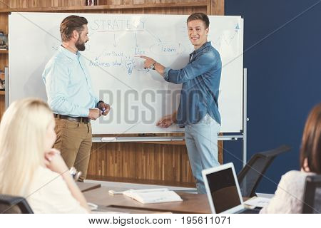 Portrait of young happy man standing near flipchart with bearded guy holding marker-pen in hands. He is pointing at information written on board by finger. Two women are sitting at table and listening