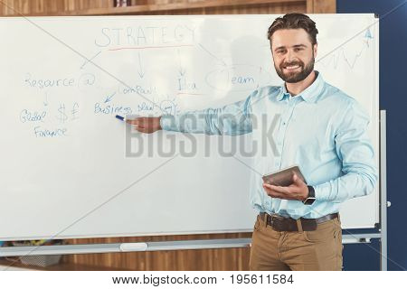 Portrait of jolly young man with beard standing beside flipchart and pointing at some important information on board by marker-pen. He is holding tablet in other hand