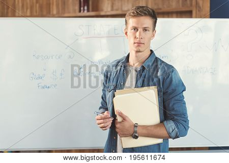 Waist up portrait of serious young man standing with his back to flipchart and holding papers and pen in hands. Copy space in left side