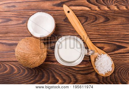 Tasteful tropical coconuts with a glass full of organic fresh milk and wooden spoon with coconut chips on a dark wooden background. Nutritious cracked coconuts on a brown table. Summer fruits.