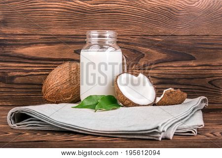 Coconuts with fresh green leaves and a mason jar of coconut milk on a light fabric and on a dark wooden background. Healthy food. Coconut and coconut milk in glass on wooden table. Tropical fruits.