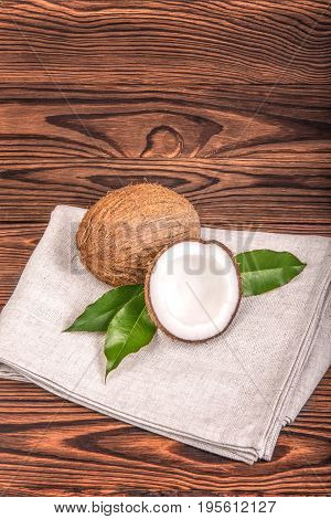 Bright brown natural tropical and fresh fruit coconuts with green leaves on a gray fabric and on a dark wooden table. Tasty tropical coconuts on a wooden table. Organic fruits.