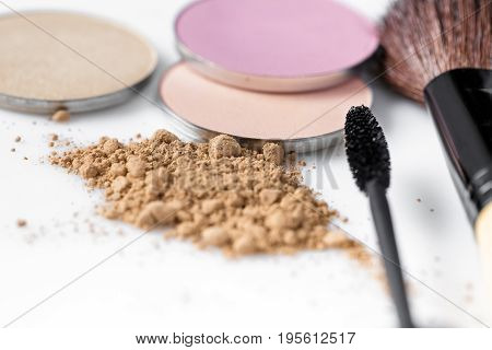 Mascara, beige powder for face, eye shadow and makeup brush on the white background. Natural makeup