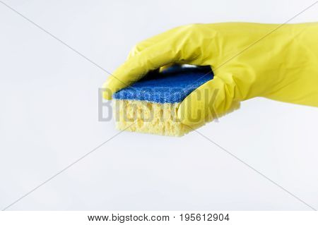 hand  in a rubber yellow glove holding sponge on white background. cleaning