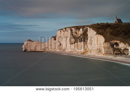 Chapelle Notre-Dame de la Garde The church on top of the cliffs at Etretat in Normandy, showing the pebble beach and the natural arch called Porte d'Amont