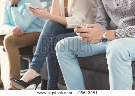 Close up of legs and hands of young man with smartwatch sitting on chair. Cross-legged woman with guy on couch and using mobile phones