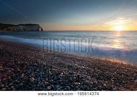 Sunset at the pebbled beach, Porte d'Aval and L'Aiguille at Etretat, a commune in the Seine-Maritime department in the Normandy region of north western France