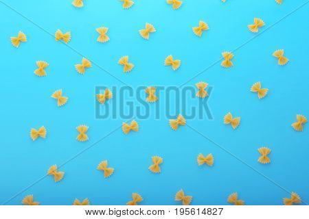 Dry macaroni in the form of butterflies are scattered on a bright blue background. Small yellow farfalle pasta. Traditional Italian food. Delicious side dish. Dry flour product.
