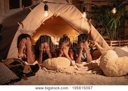Group Of Children Covering Face With Hands While Resting In Tent At Home