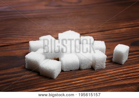 A heap of white pieces of sugar cubes for tea, coffee, baking and cooking on a wooden table. White crystals of sugar and sweet food ingredient on the table.