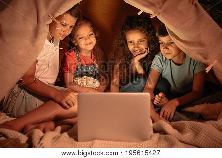 little multiethnic kids sitting tent and watching film together