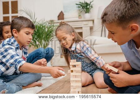multicultural group of children playing blocks wood game together at home