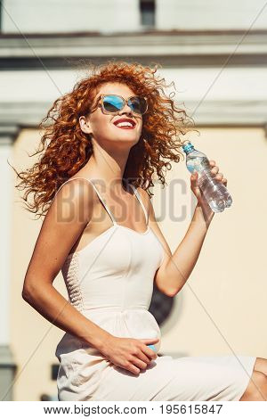 Young red haired girl in a sunglasses drinking a bottle of water. Time to travel concept. Outdoor summer portrait of young pretty cute red girl suffering summer heat. at street against city landscape.