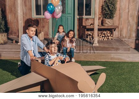 girls sitting on porch while boys playing with cardboard airplane