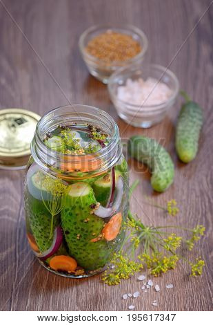 Pickled cucumbers homemade preserved on wooden table