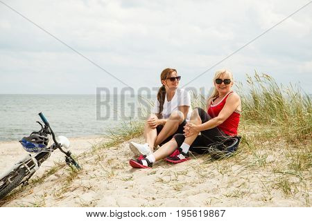 Women resting after riding bike on the beach