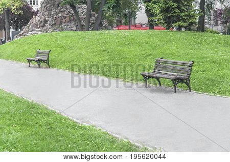 Two old rusty bench in the park in the city center