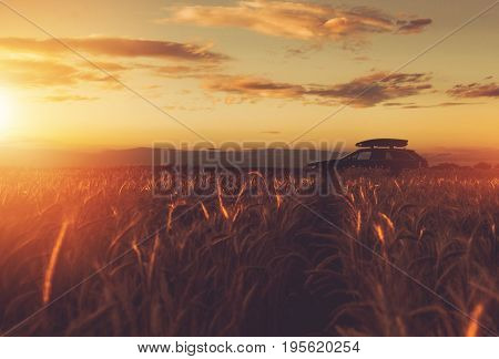Summer Countryside Getaway. Traveling Car with Roof Top Cargo Between Rye Fields During Sunset. Driving Through the Scenic Rural Countryside Landscape