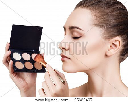 Portrait of lovely girl holding palette for contouring face. Isolated on white background.