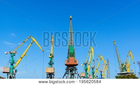 Harbor cranes on the blue sky background. Feodosia, Crimea.