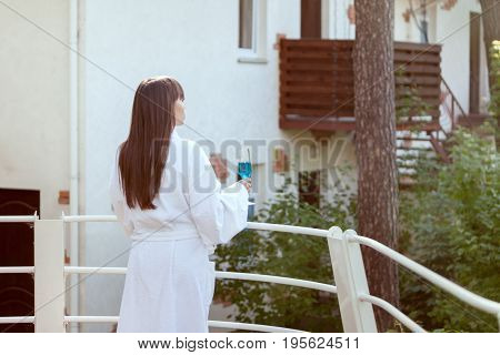 Woman with a glass of wine with her back.
