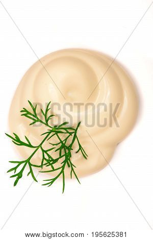Mayonnaise swirl with a sprig of dill isolated on a white background close-up. Top view.