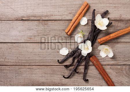 Vanilla sticks with cinnamon and flower on a old wooden background with copy space for your text. Top view.